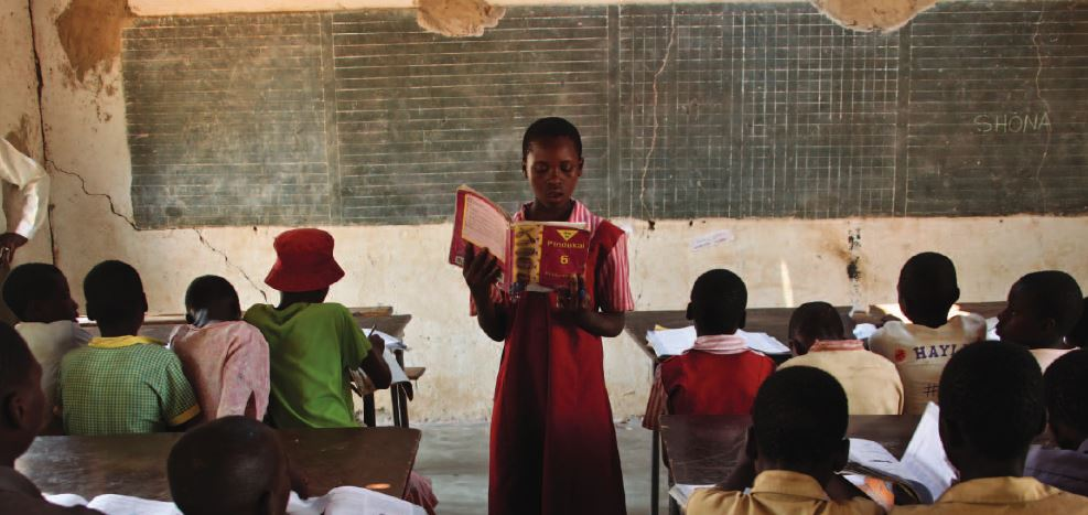 Patience, an eleven-year-old primary school student in Kachamaenza, rural Zimbabwe, reads at the front of her classroom. With help from her teacher, she can now read in her native Shona language and English // Credit: Tsvangirayi Mukwazhi / Save the Children